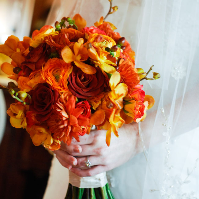 "Olivia carried a hand-tied bouquet of ""Buffalo Orange"" orchids, roses and hypericum berries."