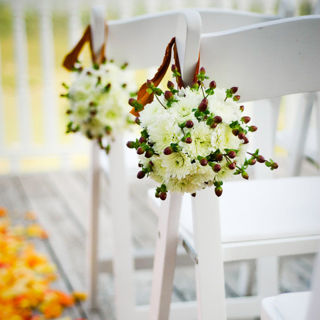 White and red pomanders hung from folding chairs lining the ceremony aisle.