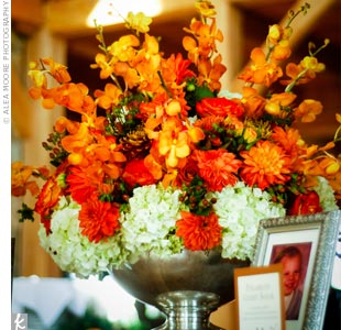 Orange dahlias, roses and hypericum berries sat in vases at the center of each table.