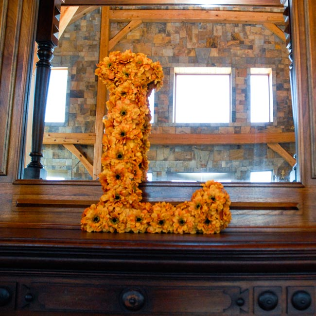 "An orange flower-covered ""L"" for the couples' last name, Lockhart, leaned against the mantel."