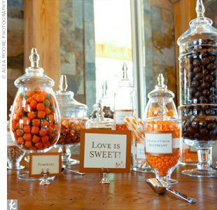 "A ""Love is Sweet"" sign hung the treats table topped with old-fashioned mason jars. Inside the jars were swizzle sticks, licorice, mallow-crème pumpkins and whoppers (the groom's favorite!)."