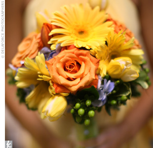 Yellow and orange roses, tulips and daisies accented with hypericum berries and blue hydrangeas achieved a fun, summer garden look.
