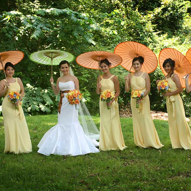 Sleeveless chiffon gowns in buttercup were light and airy, perfect to beat the summer heat. Orange parasols shaded them from the sun and added a punch of color to their attire.