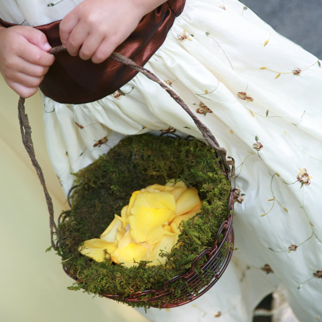 The two flower girls walked down the aisle with rose-petal filled moss baskets.