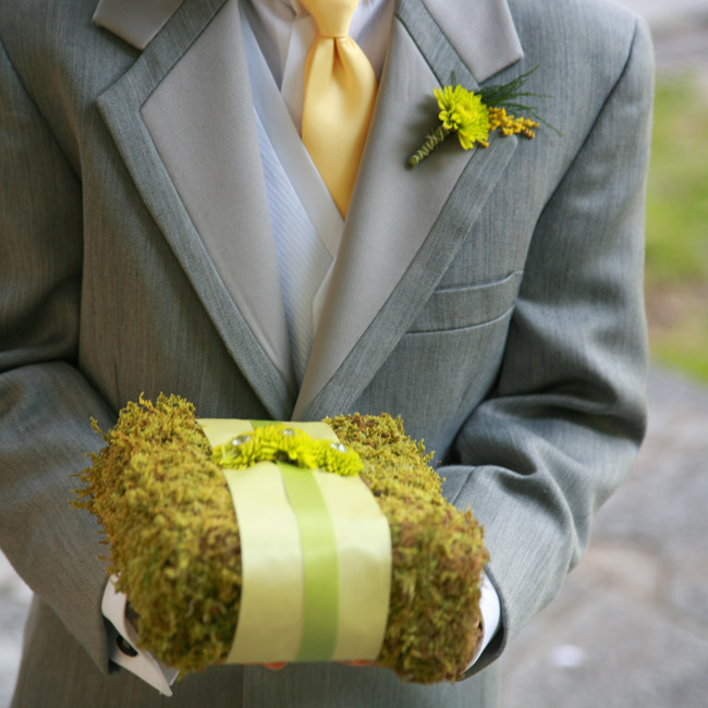 "A moss ""pillow"" wrapped with yellow and green ribbon brought the garden theme inside the church."
