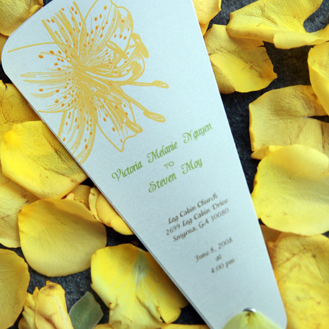 A yellow lily burst brightened blue five-leaf programs detailing the ceremony, which doubled as fans for the warm summer day.