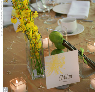 Table cards named after cities in Italy leaned against vases of Jime Storey orchids, stacked apples and bundled cinnamon sticks.
