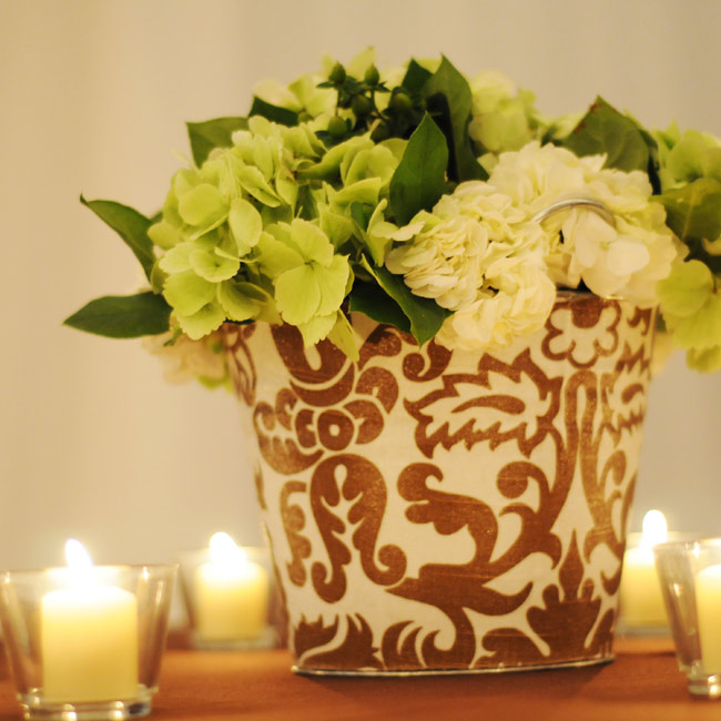 The simple arrangement of lime and cream hydrangeas didn't detract from the brown and cream printed fabric that wrapped the container. Votives added a romantic glow to the modern centerpiece.
