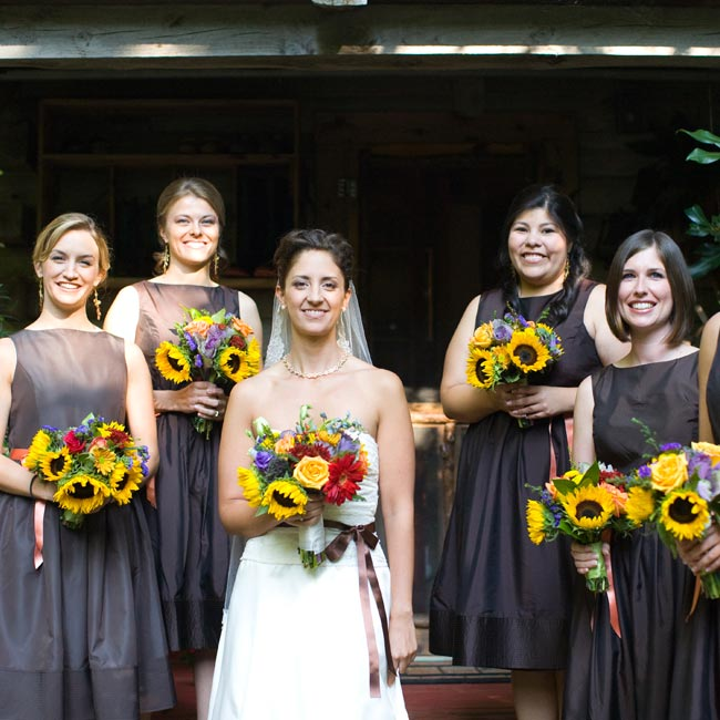 Orange ribbon belts gave a pop of color to the bridesmaids' dark, tea-length dresses. A hidden surprise: pockets for holding lipstick for touch-ups!
