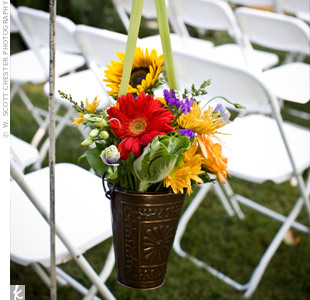 Shepherd's hooks lined the grassy aisle and held bronze pails filled with flowers similar to the ones in the bouquets.