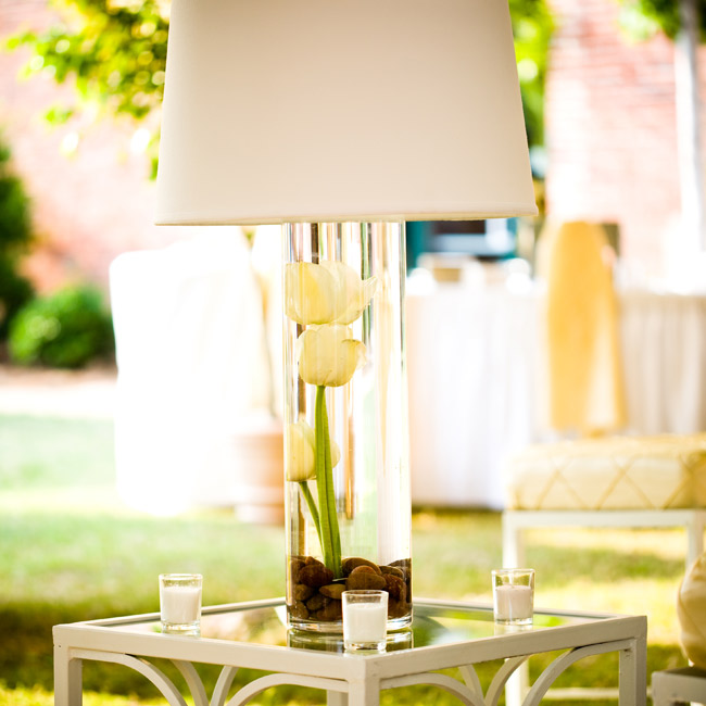 Lampshades made as big of an impact as any overstuffed floral centerpiece would make, but in a more modern way. River rocks and a few yellow tulips, the couple's signature bloom, were submerged in a cylinder vase under the shade for touches of color.