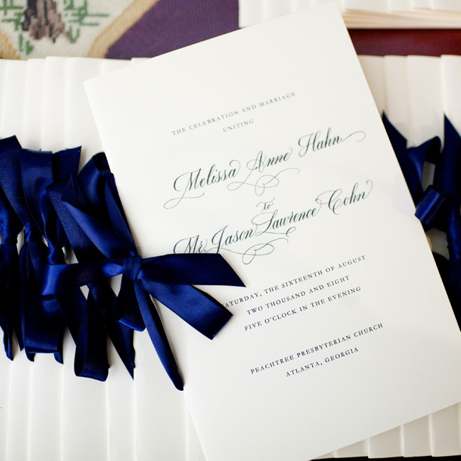 Two close friends of the couple passed out white programs printed with navy ink and tied with satin ribbons.