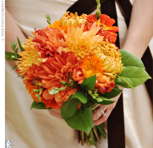 Malissa carried a bouquet of orange dahlias, mums, ranunculus, anemones, and green leaves tied with a cream-colored satin ribbon.