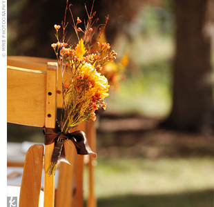 Small orange flower arrangements lined the aisle and were tied with brown satin ribbon to every other chair.