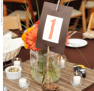 Antique mason jars filled with arrangements of orange dahlias, mums, ranunculus, and anemones worked nicely with the square tables. Malissa created small platforms for the tables using brown silk fabric, ribbon, and raffia to display the centerpieces, table numbers, and votive candles. For the table numbers (which she printed at home), she gathered ...