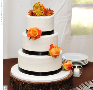 Malissa and Paul's three-tiered carrot wedding cake was covered in cream cheese frosting. It was decorated with brown ribbon, roses, and mums.