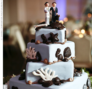 The blue wedding cake was decorated with dark chocolate seashells to incorporate the beach location. A cake topper of the couple finished it off.
