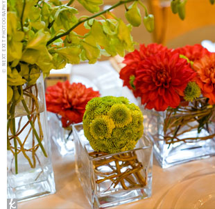 Jaymi and Kerri wanted the decor to feel very fresh, alive, and energetic. Small, collaged, red-orange arrangements topped the reception tables.