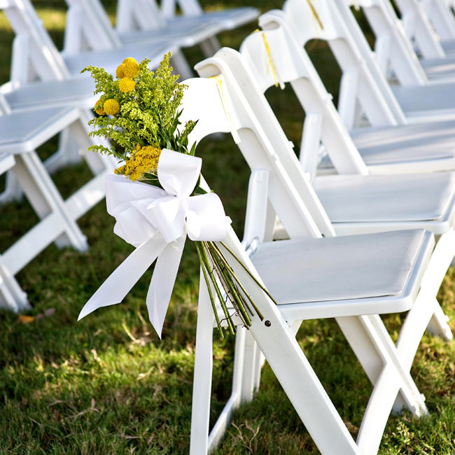 Poms and mimosa buds tied with large bows decorated the sides of aisle chairs.