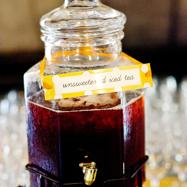 A glass drink dispenser dressed up a table with chilled iced tea for guests to cool off with before returning to the dance floor.