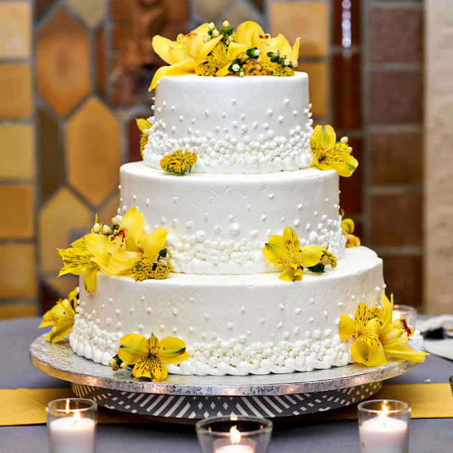 The grocery store Publix made the three-tiered buttercream cake decorated with a dot design and fresh flowers.