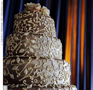 Jaenelle and Nykolas' four-tiered, chocolate-frosted wedding cake was covered in a floral white fondant design.