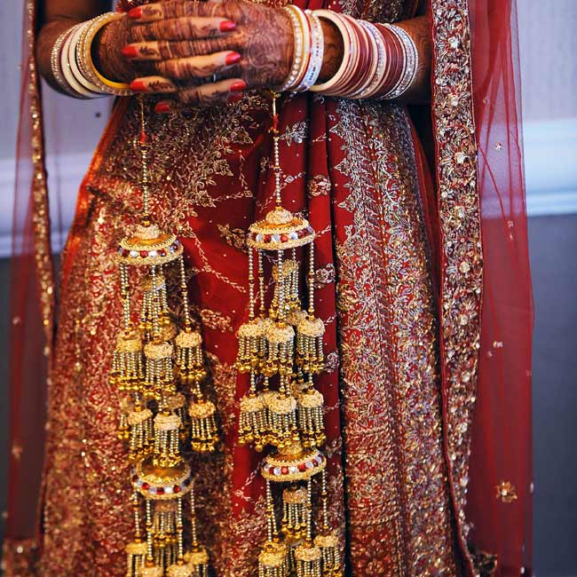 Gold bangles accessorized the bride's red-and-gold ceremony sari that she had specially made in India.