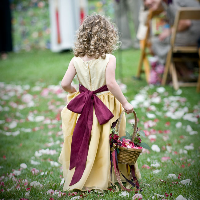 The bride's cousin wore a gold, empire-waist dress with a wine-colored sash. She carried a basket full of petals and adorned with streaming ribbons that fluttered in the wind.