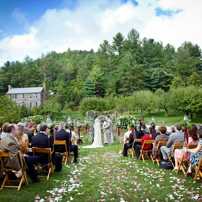 Terri and Sean exchanged vows on the front lawn of the inn beneath a bamboo frame with hanging origami cranes. Rose petals were scattered along the aisle which was lined with candleholders adorned with fresh flowers and ribbons.