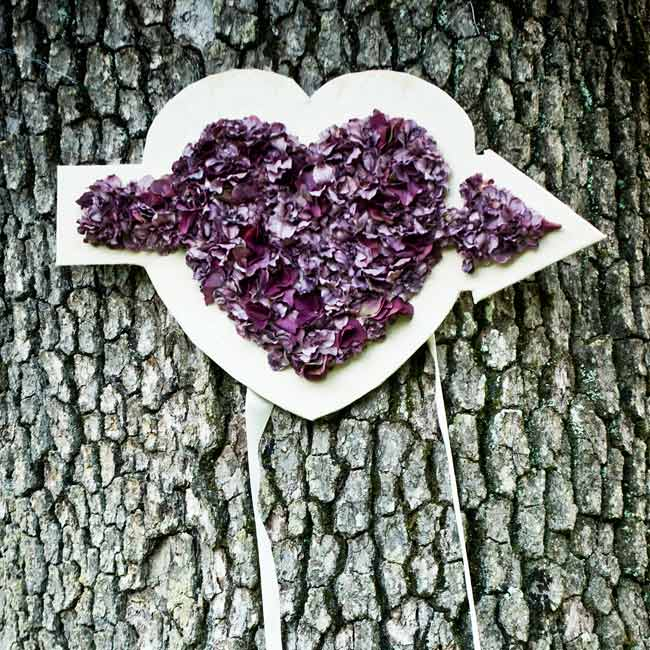 A heart with an arrow filled with purple petals decorated a tree on the property and sent guests to the reception.