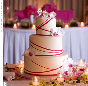 Kristin and Matthew had their three-tiered cake designed to coordinate with their invitations. The buttercream-frosted cake was accented with an azalea pink ribbon and fresh white orchids.