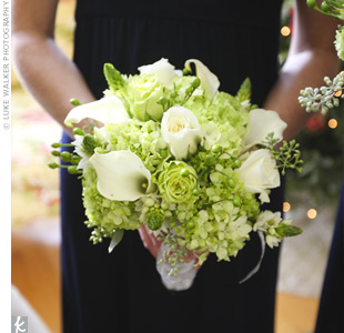Each bridesmaid carried a wintry white and green bouquet of cabbage roses, mini calla lilies, roses, hydrangeas, stars of Bethlehem, and hypericum berries all wrapped together with silver ribbon.
