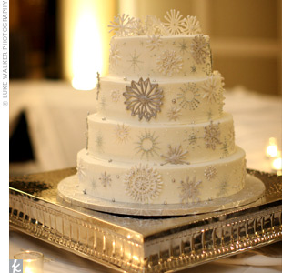 A four-tiered wedding cake was covered with white and silver sugar snowflakes and starbursts.