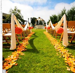 The creative couple fashioned an outdoor aisle with two rows of bright orange petals scattered in the grass.