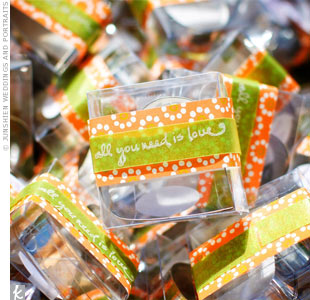"Guests took a piece of the wedding home in the form of heart-shaped cookie cutters. Each clear box was wrapped with green and orange ribbon and the wedding's theme, ""All you need is love,"" was stamped on the outside."