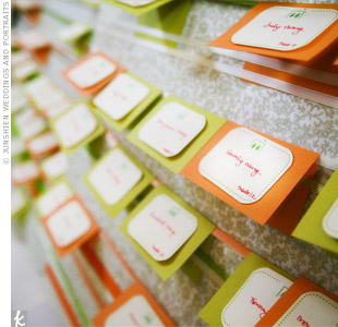 The bride handmade the escort cards in the colors of the day. Just like the fans, the cards bore the couple's signature silhouette logo.