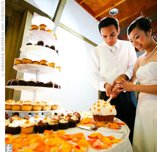 Cupcakes decorated with delicate orange flowers took the place of a traditional wedding cake. The bride and groom cut into an extra-large cupcake before each guest received their custom confections.