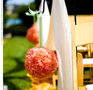 Orange pomanders hung from shepherd's hooks and billowing ivory organza strung across the chairs helped create an ethereal and whimsical atmosphere during the ceremony.