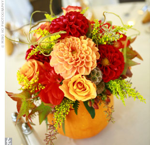 In keeping with the fall theme, tables were decorated with pumpkin centerpieces filled with vibrant flowers, including dahlias, roses, and daisies, and accented with scabiosa pods, autumn leaves, twigs, and berries.
