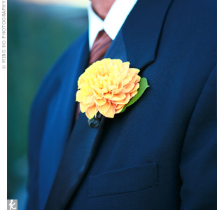The groomsmen and the couple's fathers wore single dahlia blooms as boutonnieres. The bright yellow flowers provided a sharp contrast against the classic black tuxedos.