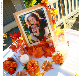 A table adorned with faux leaves and garlands displayed the couple's engagement photo, along with two memorial candles and two dahlia boutonnieres -- a tribute to the couple's grandfathers, who had passed away.