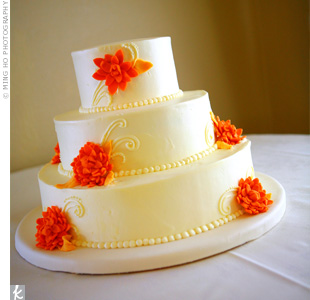 Displayed on a simple white table, the ivory buttercream cake was decorated with elegant flourishes piped on each of the three tiers. Sunny orange gum paste dahlias mimicked the flowers used in the decor.