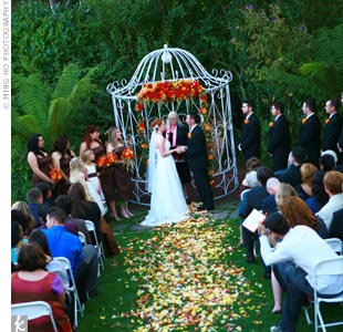 An aisle of fall leaves and rose petals led the way to the intimate garden affair. The ceremony took place under Peachwood's signature white gazebo, adorned with autumnal blooms and hanging amaranthus that reflected Carrey's bouquet.