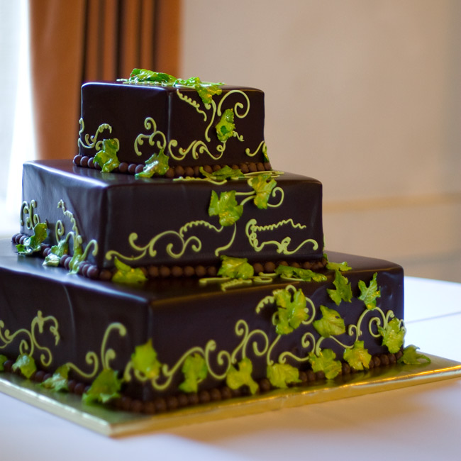 Inspired by nature (and multiple designs they saw in their bakers' portfolio), the couple chose to decorate their cake with marzipan leaves and vines. The chocolate glaze frosting and square shape kept things current.