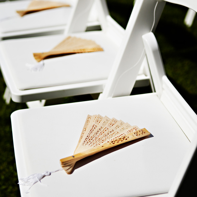 Elegant, wooden fans kept guests cool at the outdoor, summer ceremony. Bonus: the fans were all the dressing up the white chairs needed.