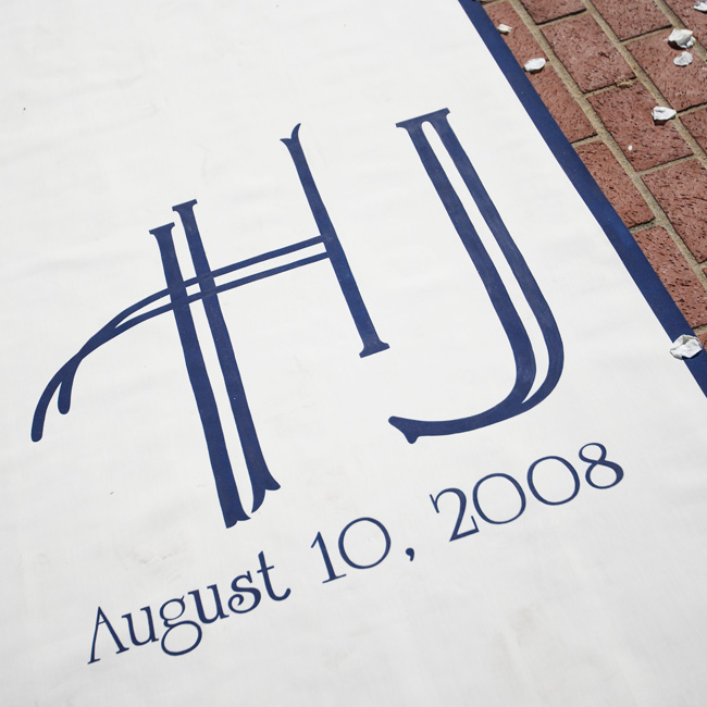 The couple personalized their ceremony by having their monogram and wedding date added to a runner. The navy and white colors tied in with their wedding day palette.