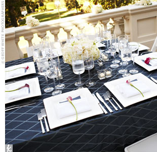 Navy linens with slate blue diamonds covered square tables. Cube vases containing candles surrounded the centerpiece of hydrangeas, roses and Phalaenopsis orchids in a square shape too.