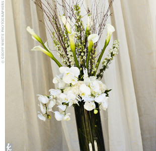 Striking arrangements of Phalaenopsis orchids, roses, calla lilies and branches marked the ceremony space. The all-white decorations kept the look crisp.