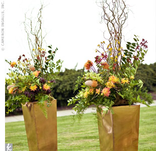 Curly willow branches and fresh flowers filled golden vases in the ceremony space.