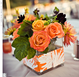 Orange-and-white printed paper wrapped around glass vases tied in the color palette, while chocolate cosmos and yellow and orange roses filled the centerpieces.